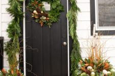 20 a greenery garland covering the doorway, a matching wreath and arrangements in pots with ornaments and pinecones