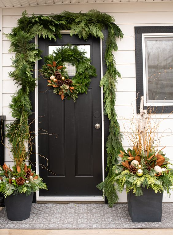 a greenery garland covering the doorway, a matching wreath and arrangements in pots with ornaments and pinecones