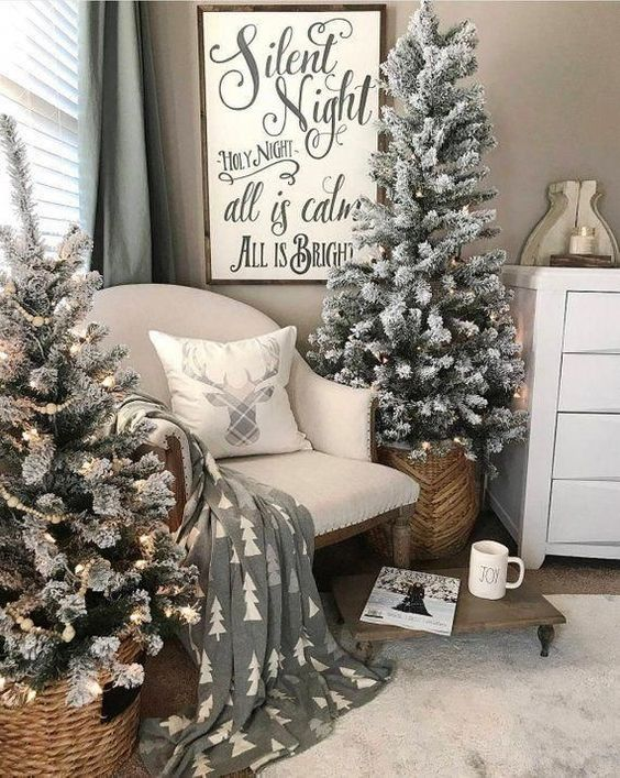 two flocked Christmas trees with lights placed into baskets are nice for a cozy farmhouse feel in the space