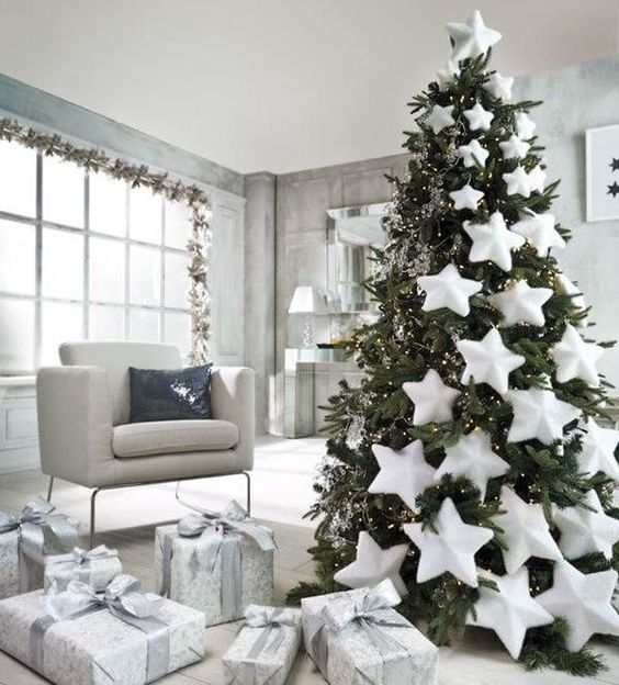 a beautiful pre-lit Christmas tree decorated with oversized white stars comign down the tree