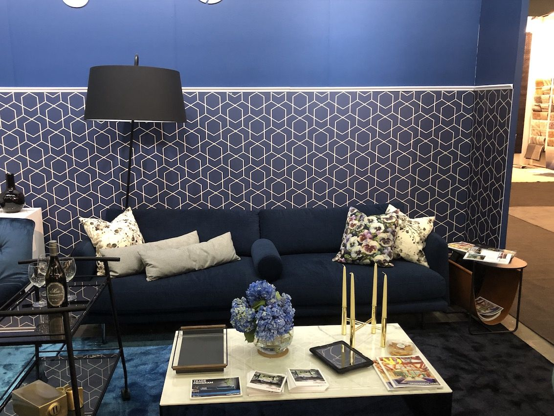a living room with a classic blue wall with added geometric prints and a matching blue rug for a trendy touch