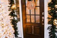 21 a lush evergreen garland with lights over the door, a flocked Christmas tree in a crate and a basket with greenery