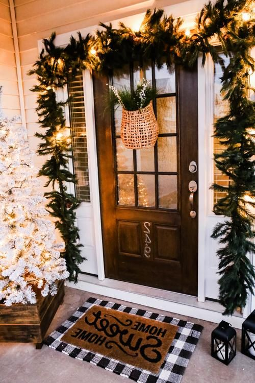 a lush evergreen garland with lights over the door, a flocked Christmas tree in a crate and a basket with greenery