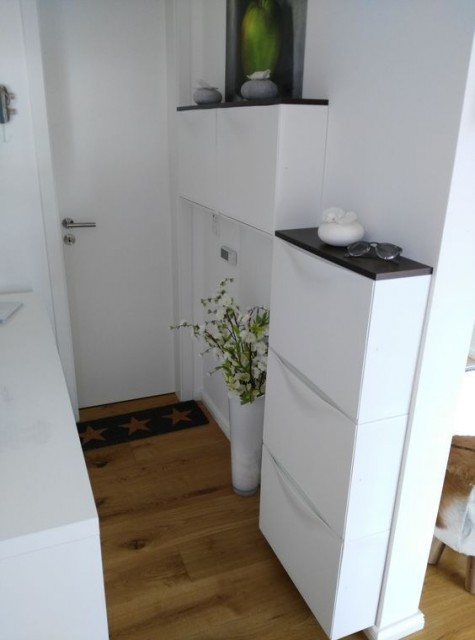 a tiny entryway done with IKEA Trones cabinets and black tabletops that are added for a contrast