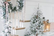 21 two non-decorated flocked Christmas trees and a matching garland attached to the railing are a gorgeous idea