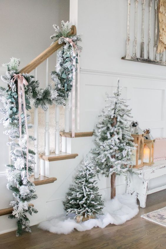 two non-decorated flocked Christmas trees and a matching garland attached to the railing are a gorgeous idea