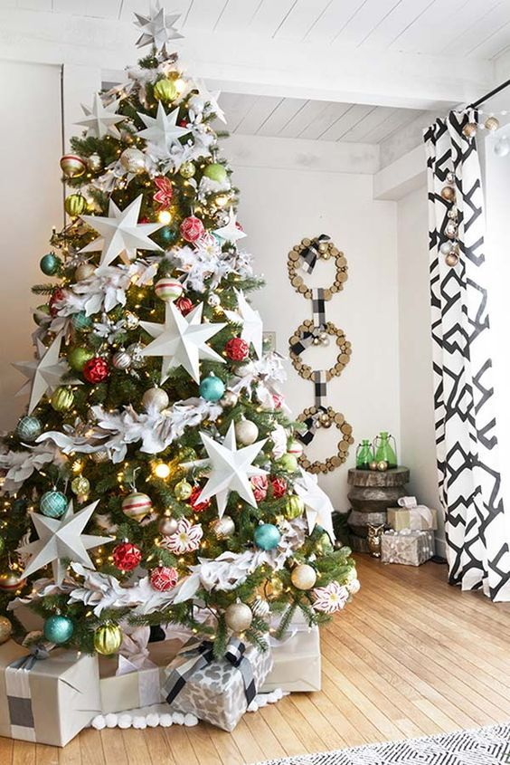 a bright Christmas tree with colorful ornaments, lights and oversized white stars looks catchy