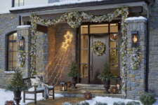 22 a pale evergreen and greenery garland with lights covering the porch and matching posies and wreaths