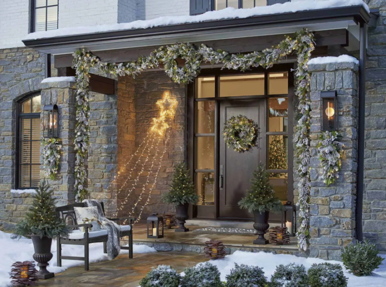 a pale evergreen and greenery garland with lights covering the porch and matching posies and wreaths