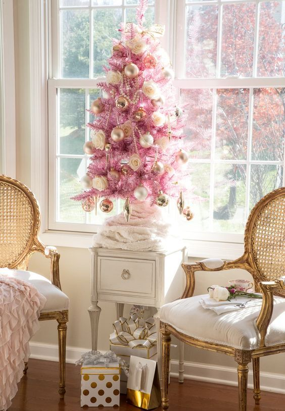 a pink Christmas tree with gold ornaments, gold beads and roses plus a bow on top looks refined and vintage like