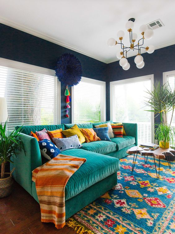 a colorful and fun living room with bright furniture, rugs, an artwork and lots of pillows