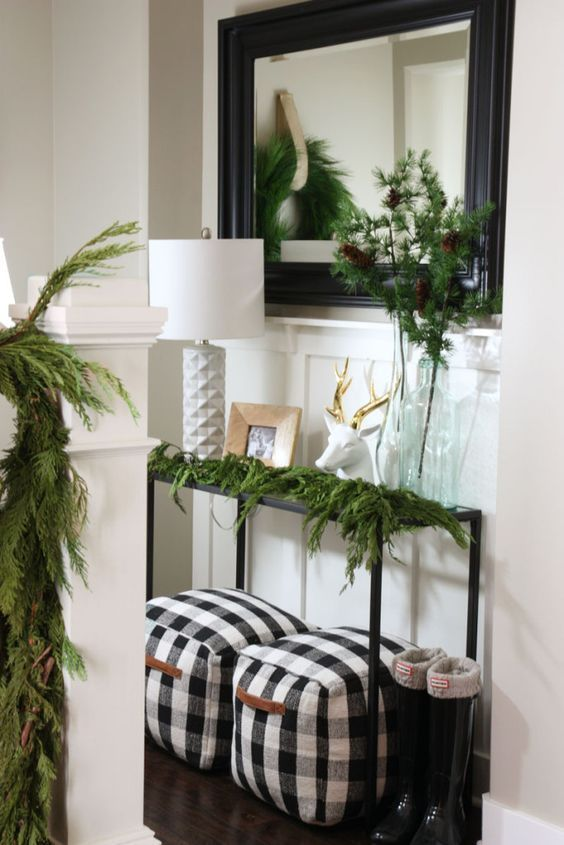a cozy farmhouse entryway decorated with evergreens and a couple of buffalo check poufs with handles