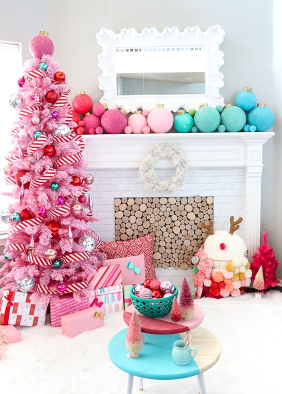 a pink Christmas tree with striped ribbons and oversized metallic and bright ornaments plus matching ones on the mantel