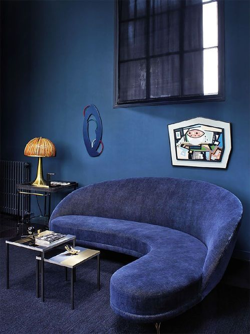 a quirky living room with a classic blue wall, a navy sofa, a cool artwork and some retro touches
