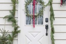 23 a simple evergreen garland covering the doorway, mini Christmas trees in pots and a greenery wreath with a red ribbon bow