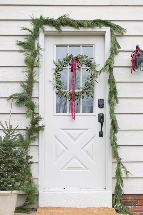 a simple evergreen garland covering the doorway, mini Christmas trees in pots and a greenery wreath with a red ribbon bow