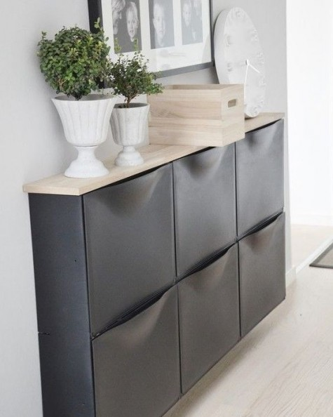 a chic IKEA Trones storage cabinet painted black and given a new top that contrasts it a lot