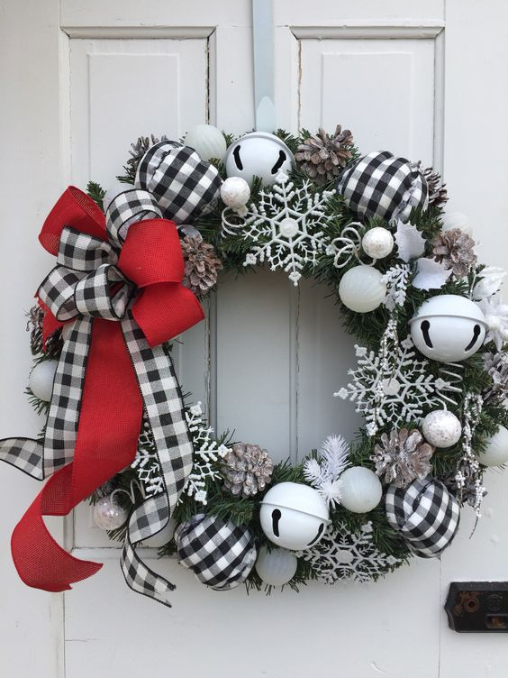 a frozen Christmas wreath with large bells, snowflakes, pinecones and a red and buffalo check bow