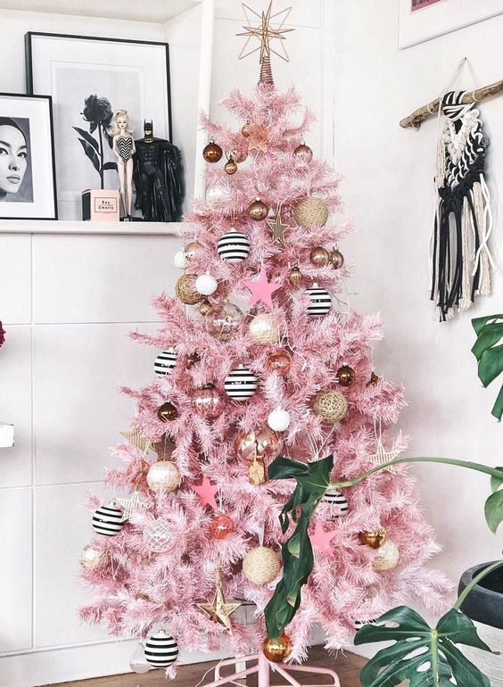 a pink Christmas tree with vine, black and white ornaments, copper and gold ones and a star topper