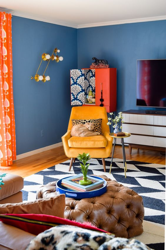 a super bright and fun living room with blue walls, colorful furniture and accessories plus textiles