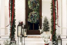 24 an evergreen garland over the porch with ribbons and bows, evergreen wreaths with pinecones and snowy Christmas trees