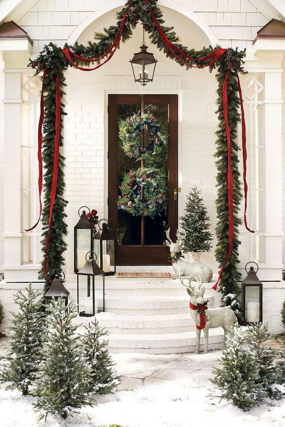 an evergreen garland over the porch with ribbons and bows, evergreen wreaths with pinecones and snowy Christmas trees