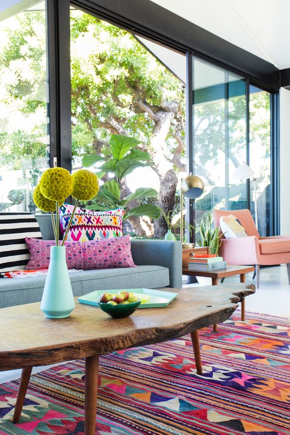 a colorful living room with bright furniture, rugs and pillows and porcelain