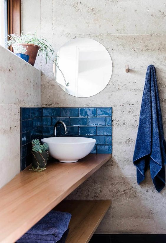 a small classic blue tile backsplash aroudn the sink and some matching towels for a bold touch in the bathroom