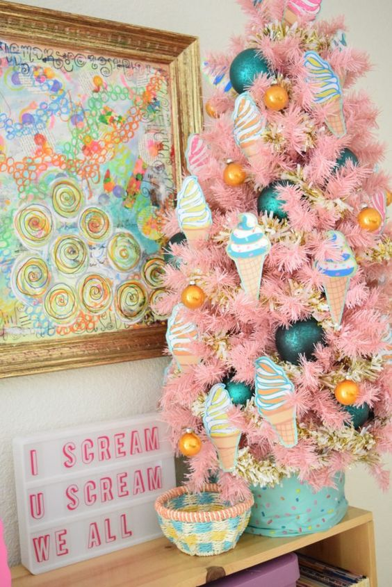 a tabletop pink Christmas tree with ice cream ornaments, marigold and teal ones of various sizes