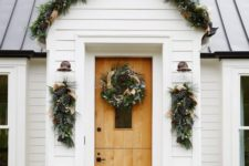 25 an evergreen garland with pinecones and burlap ribbons covering the porch and posies and wreaths that match
