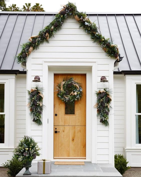 an evergreen garland with pinecones and burlap ribbons covering the porch and posies and wreaths that match