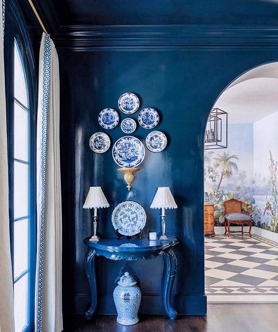 a space fully painted in classic blue - the walls, the ceiling an even a matching console table plus blue and white decorative plates
