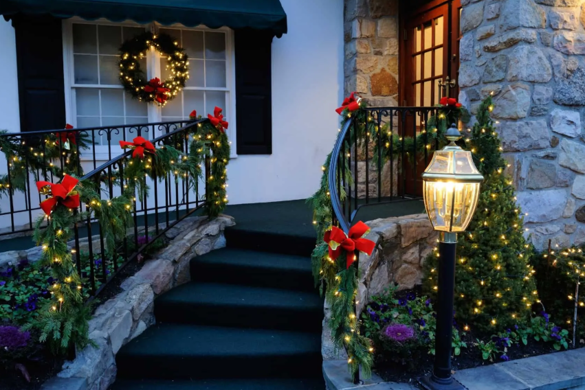 outdoor railings interwoven with lights and decorated with red bows will make your porch really festive and bright