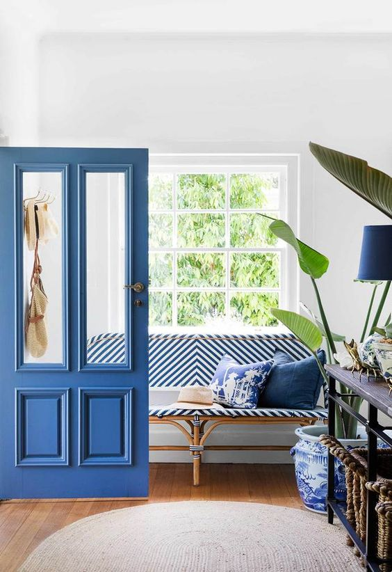a stylish entryway dotted with classic blue - a door, a lamp, pillows, a striped upholstered bench and patterned pot