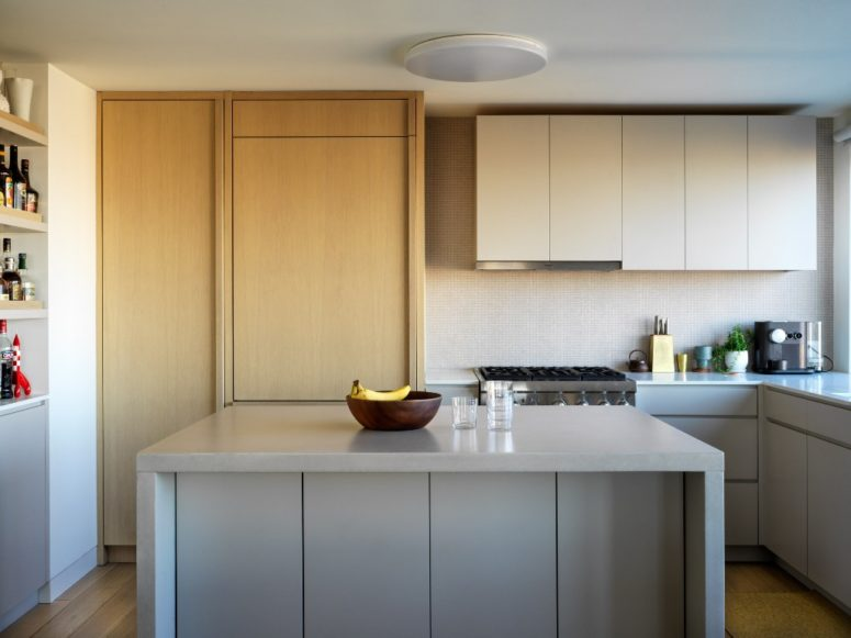 The kitchen is done in neutrals, with sleek surfaces, comfortable shelving and mostly hidden storage units