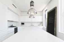 02 The kitchen is purely white, with vintage metal lamps and some stylish appliances