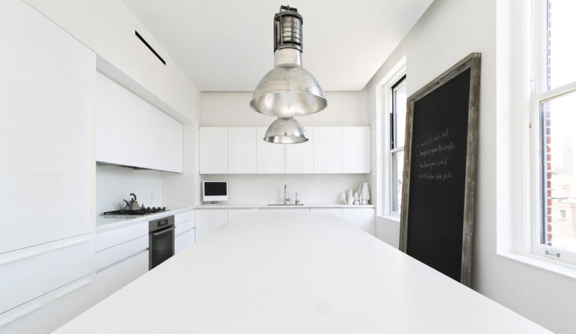 The kitchen is purely white, with vintage metal lamps and some stylish appliances