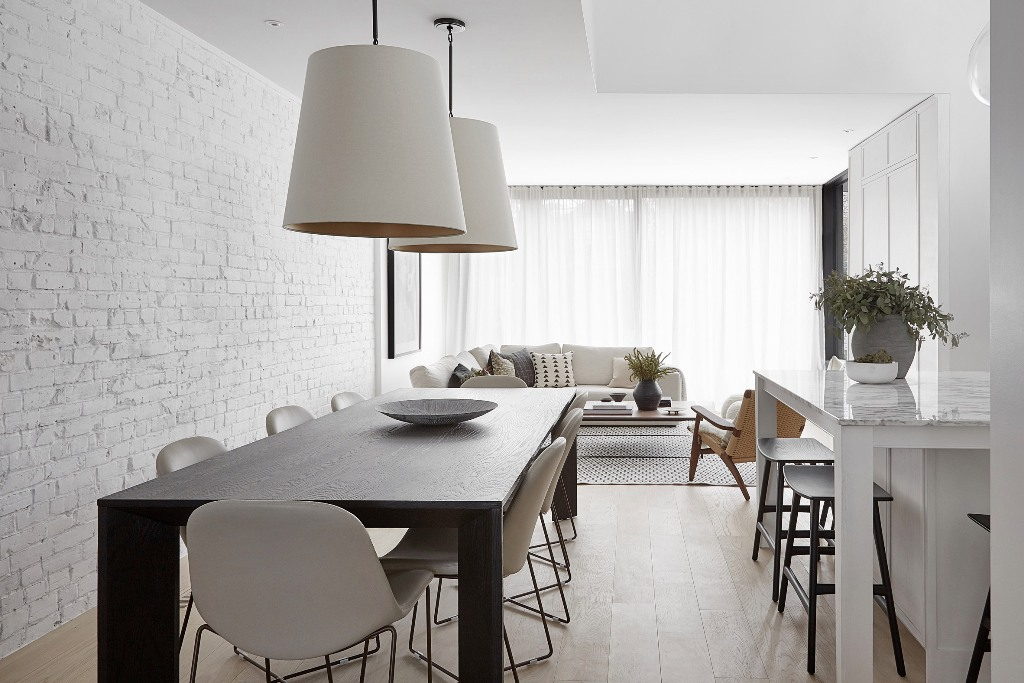 The open space unites the kitchen, dining and living room, brick walls bring texture to the space