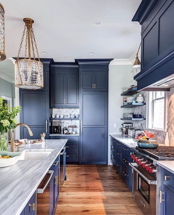 a classic navy kitchen with sleek cabinets, metal handles, stone countertops and chic and refined lamps