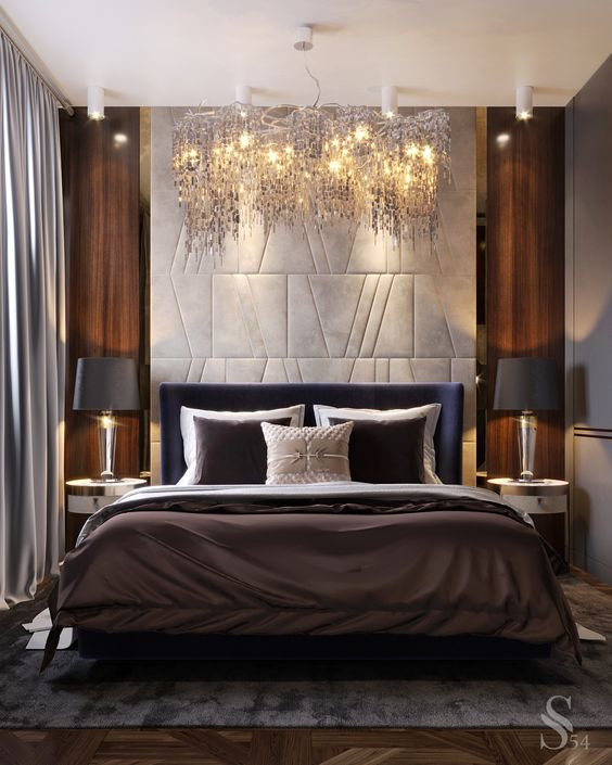 a luxurious bedroom with a stunning chandelier, cool lamps and gorgeous bedding plus a statement headboard