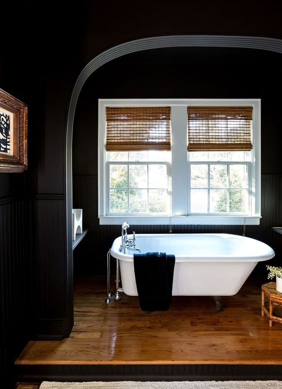 a moody bathroom with black walls, Roman shades, a wooden platform and a white bathtub