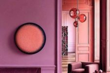 02 a pink space with molding, an elegant velvet sofa and chic spheric lamps plus parquet floors
