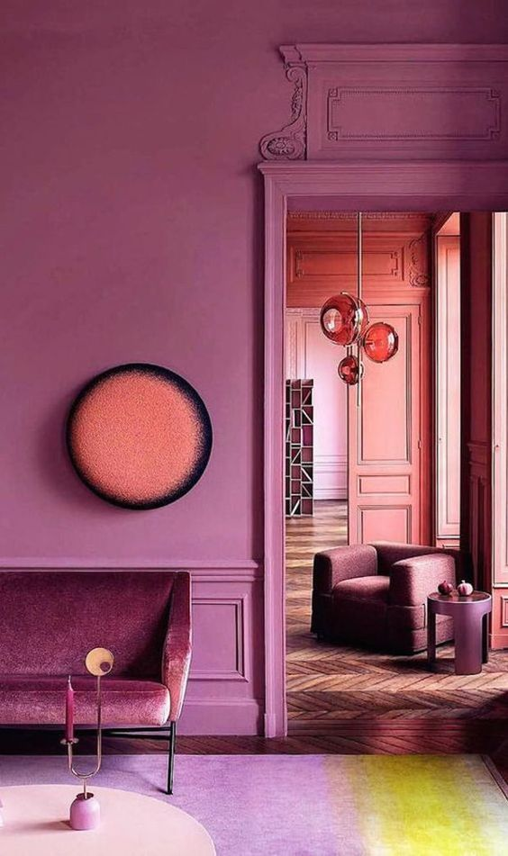 a pink space with molding, an elegant velvet sofa and chic spheric lamps plus parquet floors