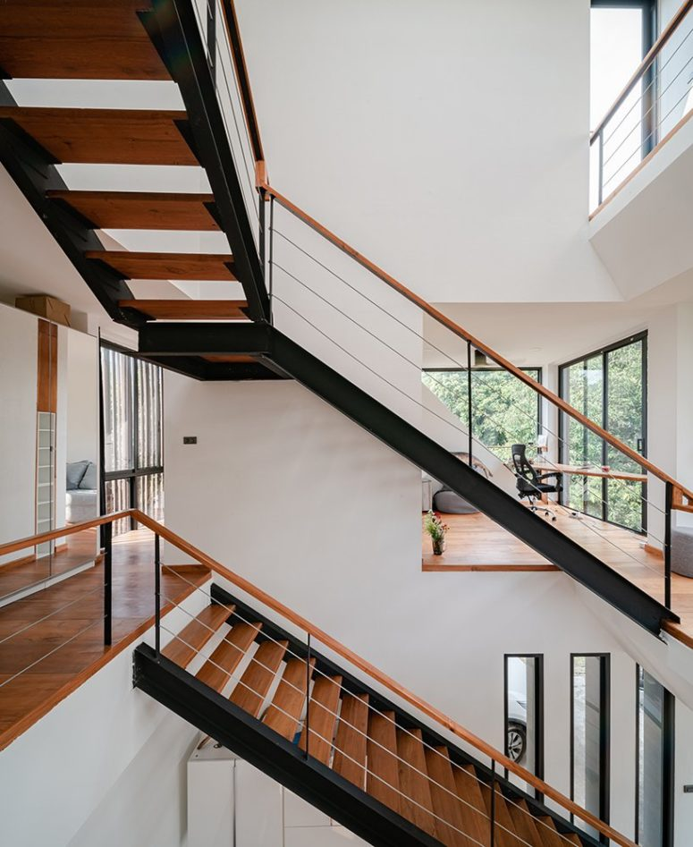 Inside, the interiors are inviting and clean, there are no unnecessary details, white walls, rich-colored wood and black touches