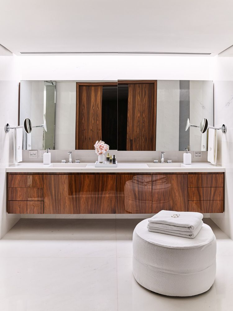 The bathroom is done with white stone, a wooden vanity and a large comfy ottoman
