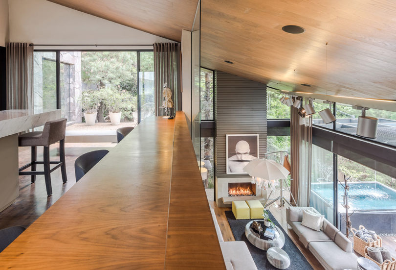 The kitchen is placed on the next level and here you can see a large kitchen island with a stone countertop and an entrance to a terrace