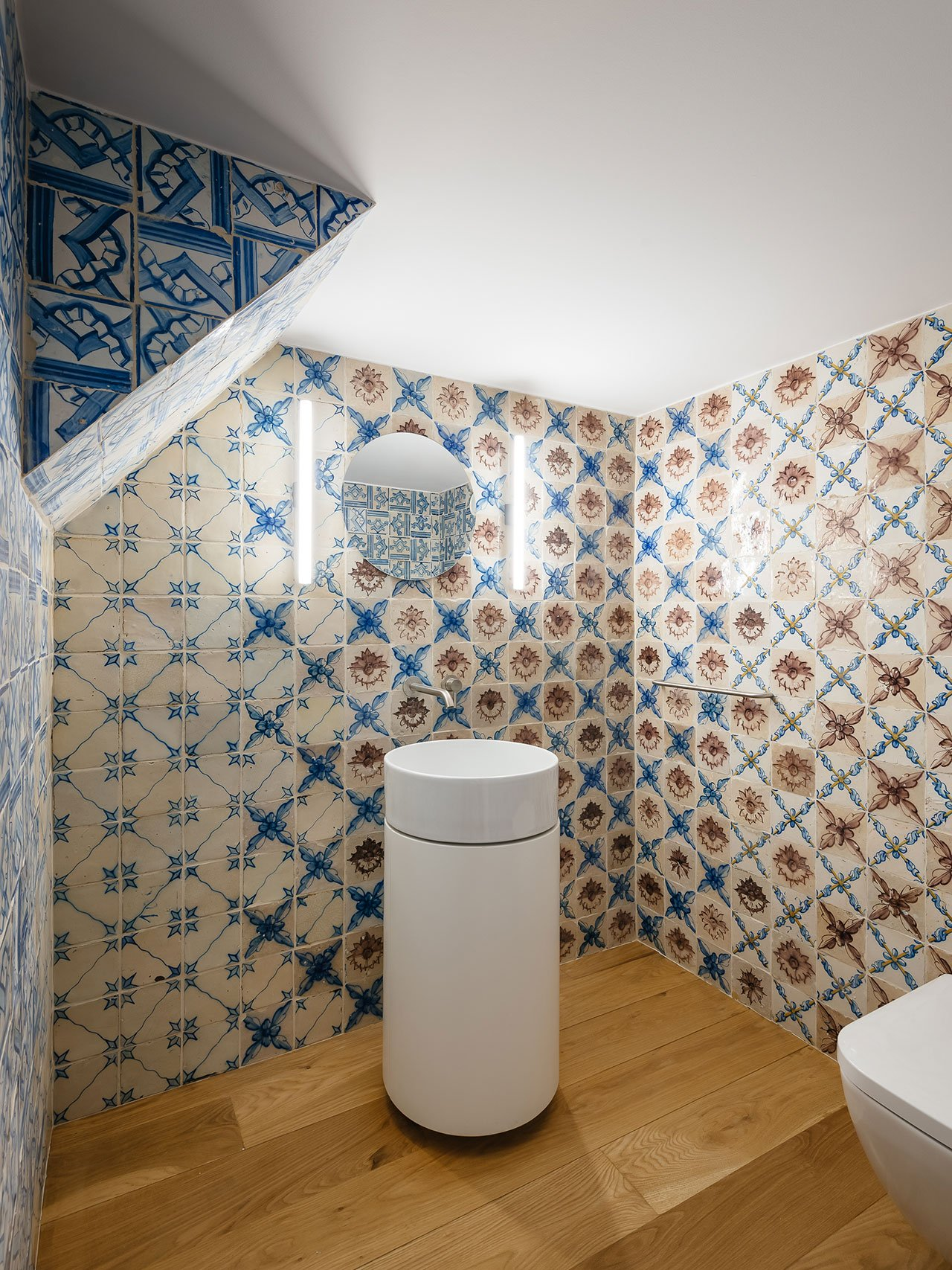 The powder room can boast of cool blue and white azulejo tiles for a bright and chic look