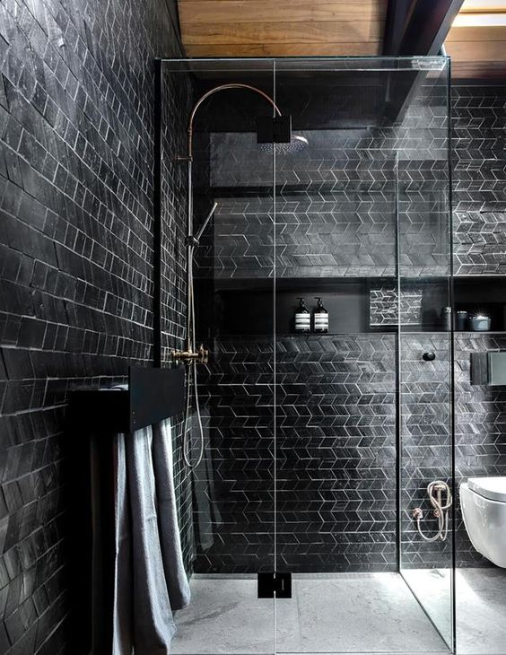 a contemporary bathroom with black tile walls and white grout plus a wooden ceiling