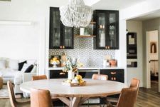 03 a round wooden table with leather chairs and a statement bead chandelier create an informal dining space