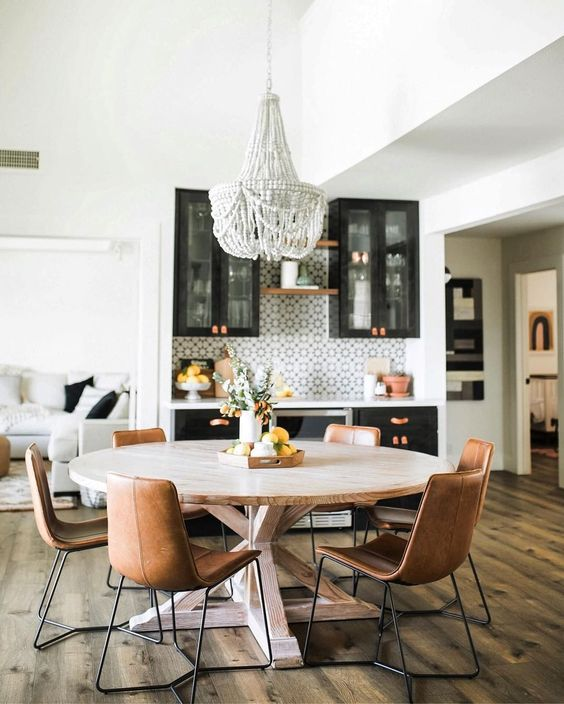 a round wooden table with leather chairs and a statement bead chandelier create an informal dining space
